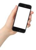 La mano lleva a cabo el espacio del iPhone 5s gris en el fondo blanco Foto de archivo