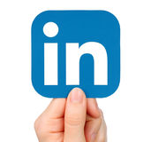 La mano lleva a cabo el icono de LinkedIn en el fondo blanco Fotos de archivo