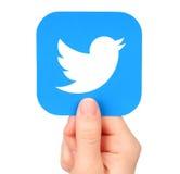 La mano lleva a cabo el icono de Twitter impreso en el papel imagen de archivo