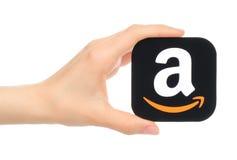 La mano lleva a cabo el icono del Amazonas impreso en el papel Imagenes de archivo