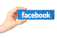 La mano lleva a cabo el logotipo del facebook impreso en el documento sobre el fondo blanco Imagenes de archivo