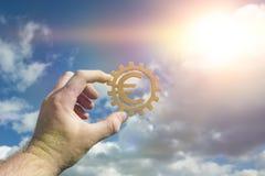 La mano lleva a cabo el símbolo euro en el engranaje en el fondo del cielo imágenes de archivo libres de regalías