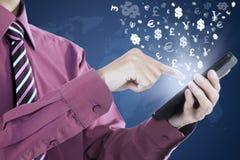La mano lleva a cabo el teléfono móvil con símbolos de moneda Imagen de archivo libre de regalías