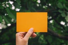 La mano lleva a cabo el trozo de papel amarillo en blanco Fotografía de archivo