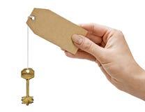 La mano lleva a cabo un clave Imagen de archivo libre de regalías