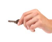 La mano lleva a cabo una pequeña llave Imagen de archivo libre de regalías