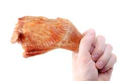 La mano lleva a cabo una pierna del hicken. Fotos de archivo