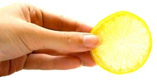 La mano lleva a cabo una rebanada del limón Imagen de archivo