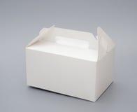 La mano lleva la caja blanca Imágenes de archivo libres de regalías