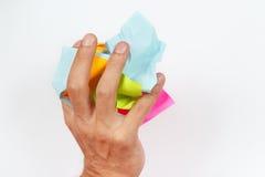 La mano machaca la basura de papel en el fondo blanco Imagenes de archivo