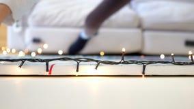 La mano macra de la muchacha alinea la cadena de la Navidad de luces en la pared almacen de video