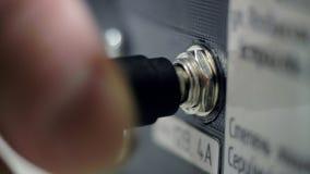 La mano macra tapa el cable en conector de la máquina-herramienta en tienda metrajes