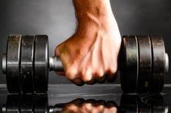 La mano maschio è barbell del metallo della holding Fotografia Stock
