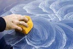 La mano maschio applica la pasta di lucidatura sulla pittura dell'automobile con la spugna Fotografia Stock