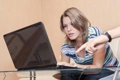La mano maschio che indica lo schermo e la donna del computer portatile segue il gesto Immagini Stock
