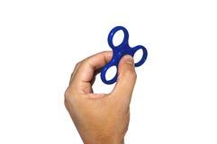 La mano maschio che tiene un filatore blu su bianco ha isolato il fondo Immagini Stock