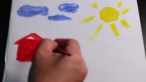 La mano maschio con la spazzola disegna la casa rossa su Libro Bianco archivi video