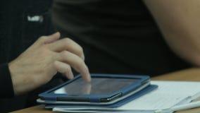 La mano maschio del primo piano scrive il testo sull'aggeggio sulla Tabella di legno stock footage