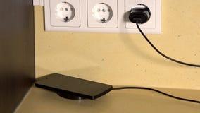 La mano maschio ha messo lo Smart Phone sul caricatore senza fili video d archivio