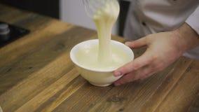La mano maschio ha montato la pastella in ciotola bianca video d archivio