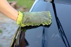 La mano maschio lava il cappuccio dell'automobile Immagine Stock