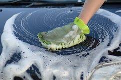 La mano maschio lava il cappuccio dell'automobile da un annaffiatoio Immagini Stock