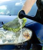 La mano maschio lava il cappuccio dell'automobile da un annaffiatoio Fotografia Stock