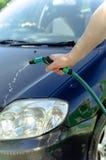 La mano maschio lava l'automobile con un tubo flessibile Immagine Stock