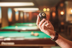 La mano maschio mostra una sfera il numero otto del biliardo Immagini Stock