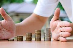 La mano maschio protegge la pila delle monete dei soldi con la casa Immagine Stock