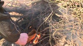 La mano maschio prova ad infornare sul camino con i ramoscelli dell'albero e della carta stock footage
