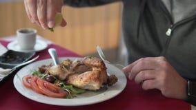 La mano maschio schiaccia il succo di cedro sul pollo affumicato video d archivio