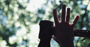 La mano maschio tiene un'ascia sui precedenti della foresta Boscaiolo del primo piano nella foresta con un'ascia in sue mani stock footage