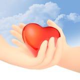 La mano maschio trasferisce il cuore di vetro rosso ad una mano femminile Fotografia Stock