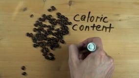 La mano masculina anota el contenido calórico de los granos de café en superficie de madera almacen de video