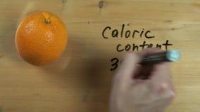 La mano masculina anota el contenido calórico de la naranja en superficie de madera metrajes