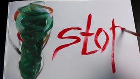 La mano masculina con el cepillo escribe la parada de la palabra en el Libro Blanco con el dibujo abstracto multicolor almacen de video