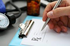 La mano masculina del doctor de la medicina escribe la prescripción al paciente Fotos de archivo libres de regalías