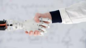 La mano masculina del prosthetist del doctor sacude la prótesis robótica de la mano en centro médico metrajes