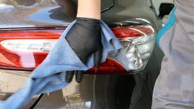 La mano masculina del trabajador con el paño limpia descensos del agua de la linterna posterior después de lavar el coche metrajes