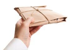 La mano masculina entrega el sobre lleno imagen de archivo libre de regalías