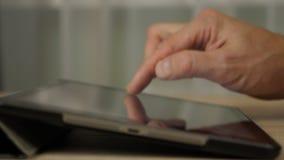 La mano masculina escribe el texto con el finger en la tableta Vista lateral Ascendente cercano del extremo almacen de video