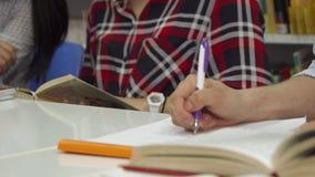 La mano masculina escribe en cuaderno en la biblioteca almacen de video