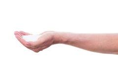 La mano masculina está sosteniendo el sulfito o la sal fotos de archivo