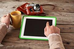La mano masculina hace clic entonces la tableta de la pantalla en blanco en la tabla de madera y sostener una taza de primer del  Fotografía de archivo libre de regalías