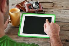 La mano masculina hace clic la tableta de la pantalla en blanco en el primer de madera de la tabla Foto de archivo libre de regalías