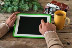 La mano masculina hace clic la tableta de la pantalla en blanco en el primer de madera de la tabla Imagen de archivo libre de regalías