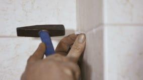 La mano masculina martilla el pasador en la pared almacen de metraje de vídeo