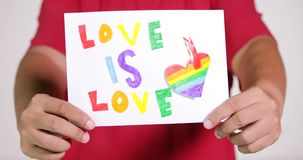 La mano masculina muestra el papel con la bandera de LGBT metrajes