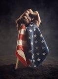 La mano masculina protege la bandera americana Imagen de archivo libre de regalías